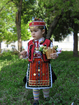 Traditional costume for a child from Nikopol, Bulgaria. Pishtimal, apron, vest, head ornaments, belt